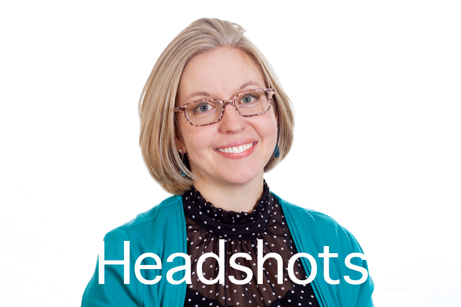 Headshots button. This Brian Charles Steel photo is a headshot of a white woman with blonde hair.  She is wearing glasses, a light blue green sweater and a black blouse with white polka dots.  She is centered in the frame, and the background is completely white.  The woman is lit with a Rembrandt style of lighting.