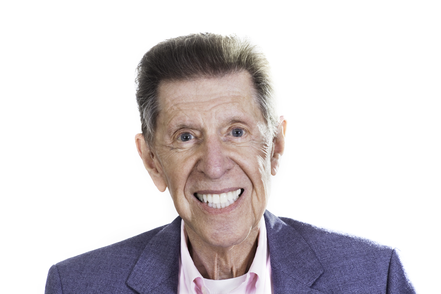 This Brian Charles Steel photo is a headshot of an older white gentleman.  He is wearing a light blue sport coat with a pink dress shirt.  He has reddish hair and blue eyes.  He is centered in the frame and the background is completely white.  He has a big smile, and he is lit with Rembrandt style lighting.