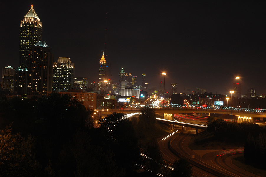 A nighttime skyline shot of midtown Atlanta. It depicts several towers along with the banana bridge and the connector.  The long exposure has caused the car lights to be beams of light. Photography by Brian Charles Steel.