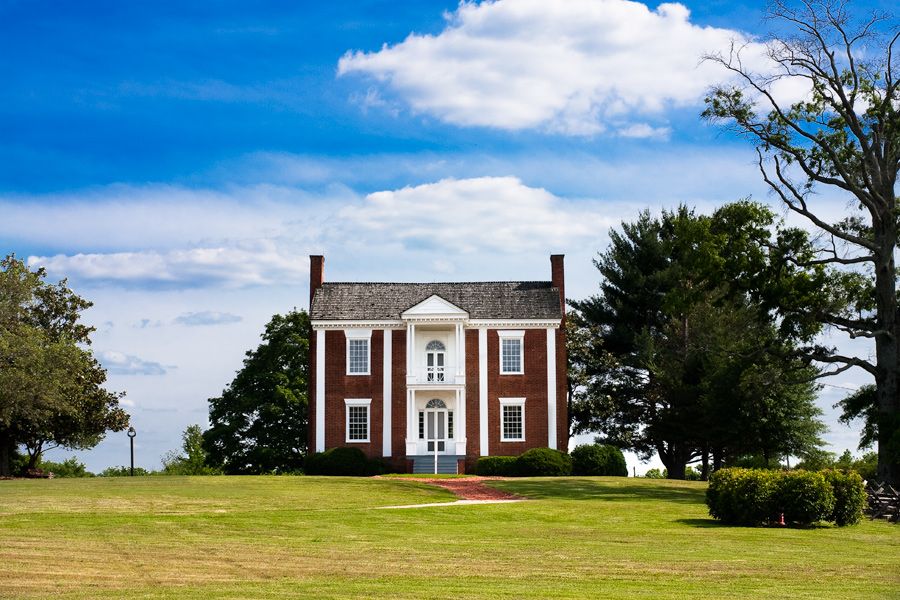 This is a Brian Charles Steel photograph of Chief Vann's house on a sunny day in Chatsworth, Georgia.  The house is made of red brick with white pillars, and a white balcony in the middle of the second floor in the front.  The house is situated in the middle of the frame with blue sky above and short green grass below.