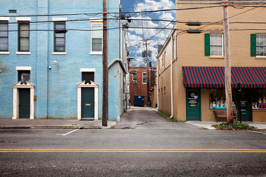 This is a Brian Charles Steel photograph of downtown Cleveland, Tennessee.  A light blue building and a tan building fill the top three quarters of the frame, with an alley and blue sky between them.  The alley has a dark blue dumpster in the back.  A street fills the bottom quarter of the frame with a bright yellow line stretching across the middle of it.