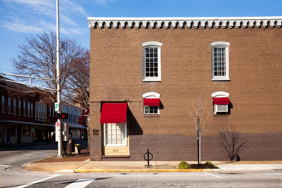 This is a Brian Charles Steel photograph of the outside of Café Roma in Downtown Cleveland, Tennessee.  The building a red brick with white trim.  The windows have white trim and red awnings.  The building takes up the right three fourths of the frame.  The sun beats down on the building while the street to the left of it remains in shadow.