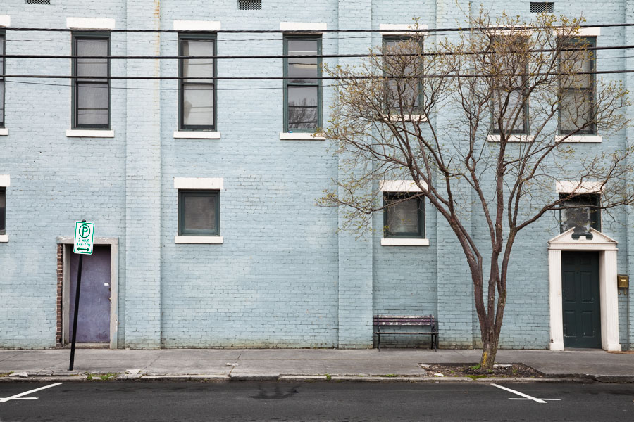 This Brian Charles Steel photograph depicts a light blue building with dark framed windows surrounded by white bricks.  The right half of the frame contains a tree without leaves.  There are protruding rectangles composed of bricks extending from the front of the building.  The rectangles go all the way up the building like pillars.  On the far right side there is a green door surrounded by white trim.  To the left of the door between two brick rectangles is a park bench with worn wood.  On the far left side of the frame is a faded purple door behind a one-hour parking sign.