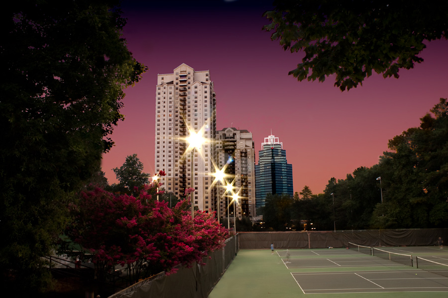 This is a Brian Charles Steel photograph of Park Towers and the King building in Sandy Springs Georgia at sunset.  The towers and king building are in the middle ground.  In the foreground are tennis courts on the right.  On the left in the foreground are trees and bushes with pink flowers.  In the background is an orange and purple sunset sky.  The streetlights in front of the buildings twinkle like stars.