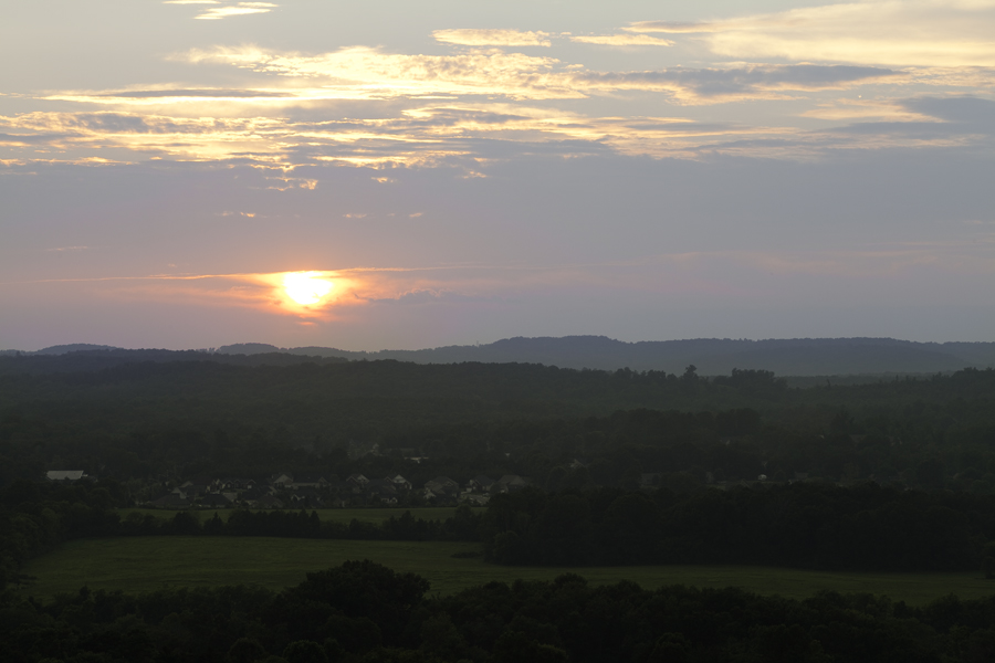 This Brian Charles Steel photo depicts a landscape at sunset in Cleveland, Tennessee.  The sun is towards the middle portion of the frame on the right side of the image.  Below the sun are green mountains covered with trees, and a grass plain. The plain is towards the bottom of the image, and below it in the foreground are more trees.  Just above the plain on the right side is a large cluster of houses on the side of a mountain.  The sky occupies the top half of the frame the bottom portion of the clouds are bluish mixed with streaks of orange from the sun.  The clouds above that portion of the sky are orange and yellow with a few blue streaks.