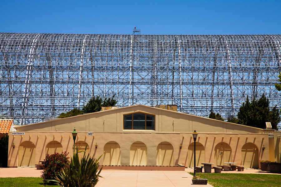 This Brian Charles Steel photo depicts a conference building at NASA Ames Research Center in Mountain View, California.  The building is tan, and has nine arches.  It has a triangular shaped roof with a pentagon shaped window towards the top. The building is in the top of the bottom third of the frame.  Behind the building is a much larger metal frame of a hanger that used to house aircraft.  Behind the hanger is a clear blue sky that takes up about two thirds of the frame.