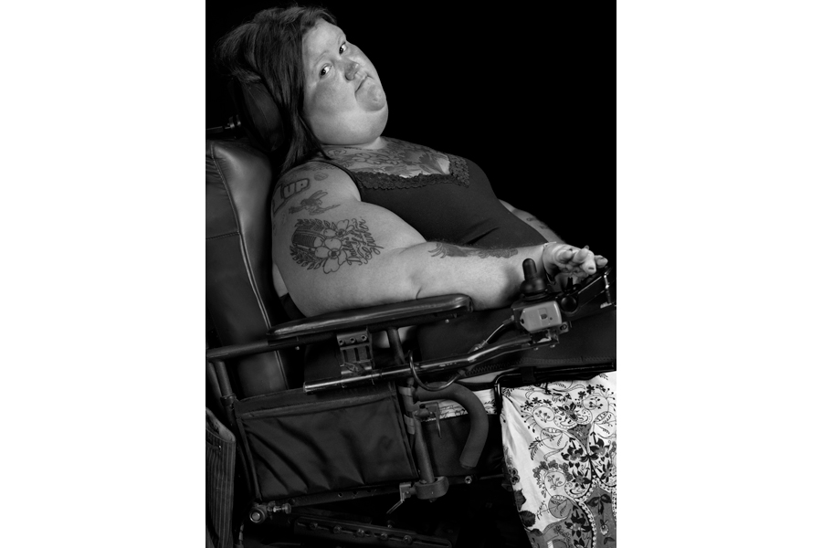 This is a Brian Charles Steel black and white photographic portrait of Jessica Blinkhorn.  She is sitting in her black electric wheelchair.  Her body is facing the right side of the frame at a slight upward angle.  Her head is turned toward the front, and she looks into the camera with a relaxed smile.  She is wearing a dress, and her arms are covered with tattoos. The background is solid black.