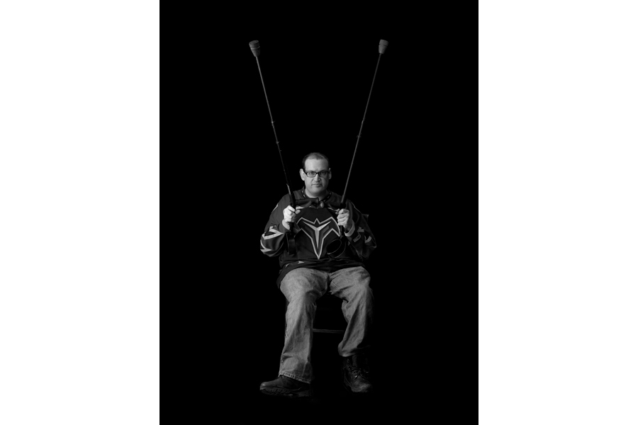 This is a Brian Charles Steel black and white photographic portrait of Ben Kitchings.  Kitchings is in his thirties, and has cerebral palsy.  He is wearing glasses, a Thrashers jersey, and jeans. His whole body is in frame, and he is positioned toward the bottom of the frame.  He holds his crutches up in the air making a v.