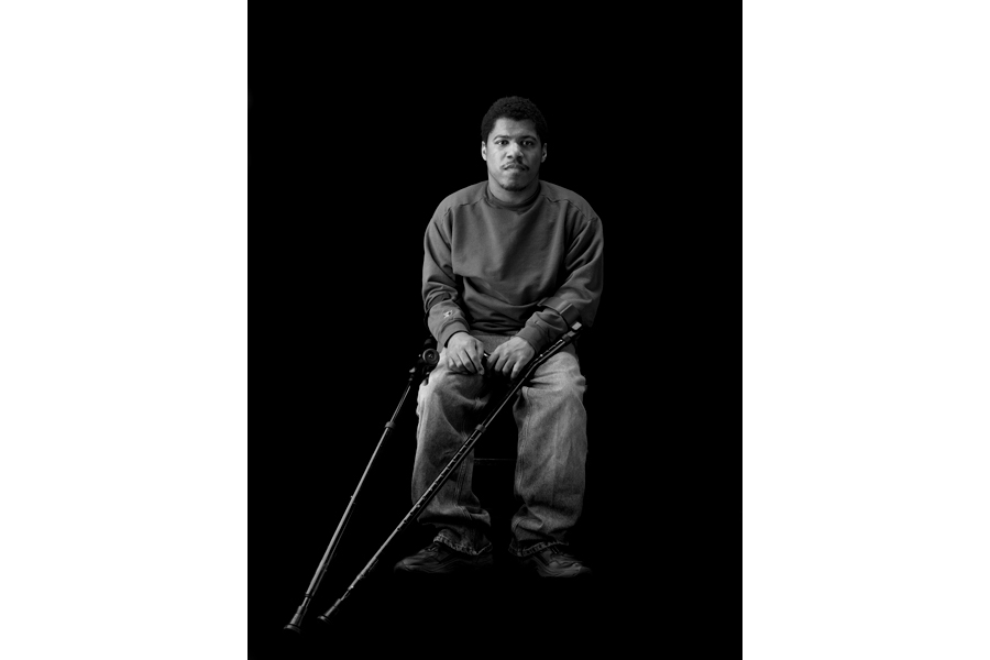 This is a Brian Charles Steel black and white photographic portrait of Charlie White.  Charlie is a thirty-year-old African American with cerebral palsy. His full body is in frame and takes up about one third of the image.  He is wearing a long sleeved sweater and blue jeans.  He is sitting in a chair towards the center of the frame.  His crutches are pointed diagonally towards the bottom left corner.  He is lit in a Rembrandt style with the main light source coming from the left.  He is looking directly into the camera.