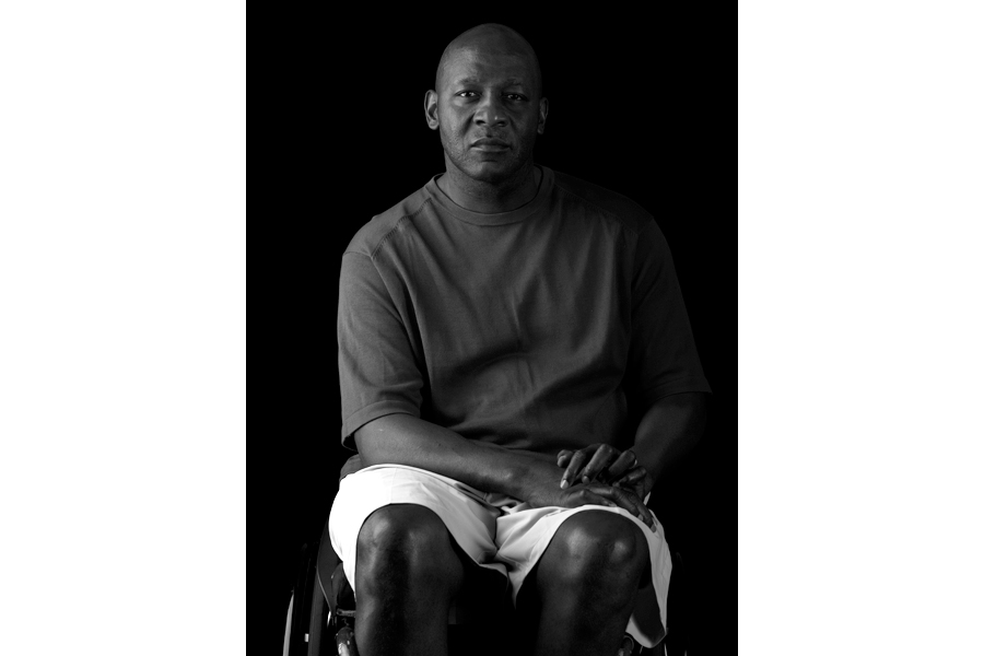 This is a Brian Charles Steel black and white photographic portrait of Curtis Lovejoy.  Lovejoy is wearing a dark short-sleeved shirt and white shorts.  He is seated in his wheelchair and is facing forward.  He is looking straight into the camera and is shown from the knees and up.  His hands are in his lap.  Lovejoy is lit from the left in a Rembrandt style. The background is solid black.