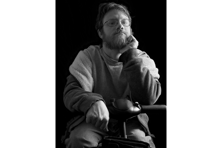This is a Brian Charles Steel black and white photographic portrait of Eric Carlisle sitting in his scooter.  He is wearing glasses, and looking directly into the camera.  He is wearing a sweater and jeans.  Carlisle is lit in a Rembrandt style with the main light source coming from the right.  He is shown from the knees up, and comprises most of the image.