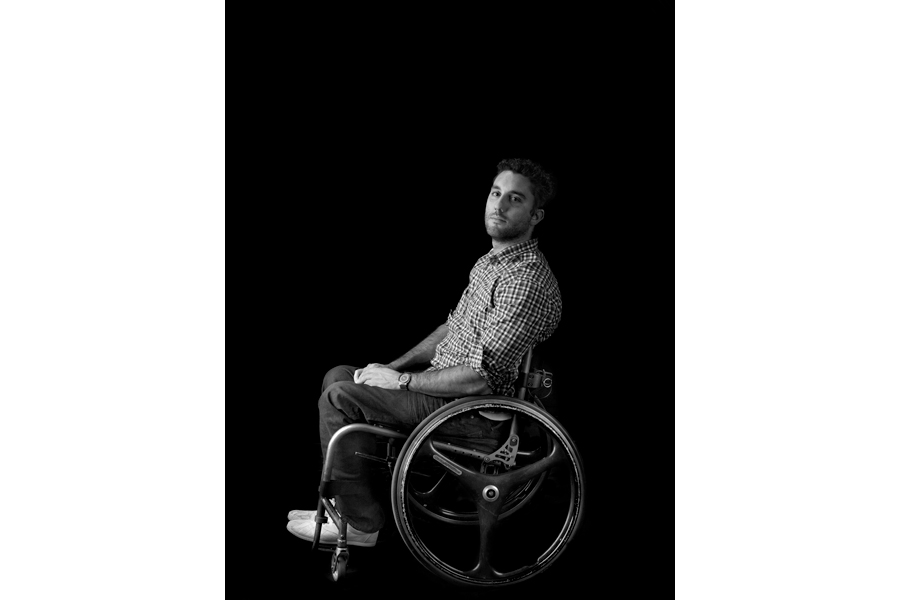 This is a Brian Charles Steel black and white photograph of Kyle Benedict.  He is paraplegic, and sitting in his wheelchair towards the bottom center of the frame.  His chair is facing the left, but he is turned toward the camera looking straight into it.  His hands are folded neatly in his lap.  Benedict has short hair and an athletic build.  The main light source is coming from the left.